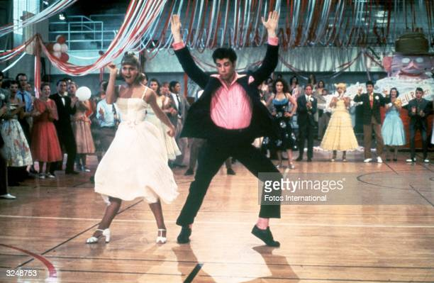 Australian singer and actor Olivia NewtonJohn and American actor John Travolta dance in a crowded high school gym in a still from the film 'Grease'...