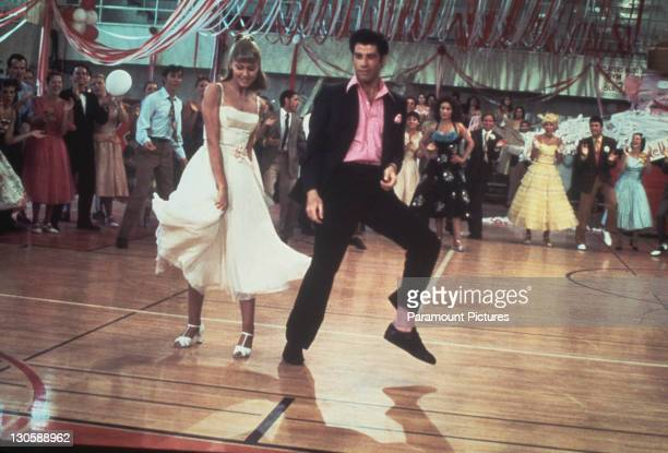 Australian singer and actress Olivia NewtonJohn and American actor John Travolta dance in a crowded high school gym in a still from the Paramount...