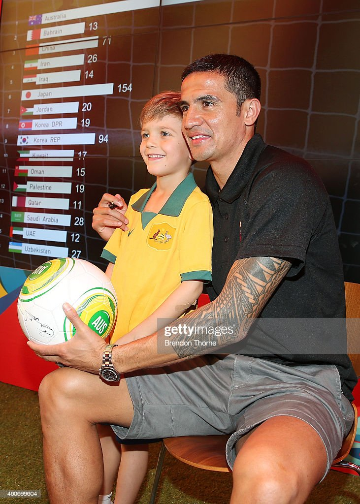 Australian Socceroos player Tim Cahill poses with a young fan during the launch of the Football Fan Park at Customs House on December 20, 2014 in Sydney, Australia.