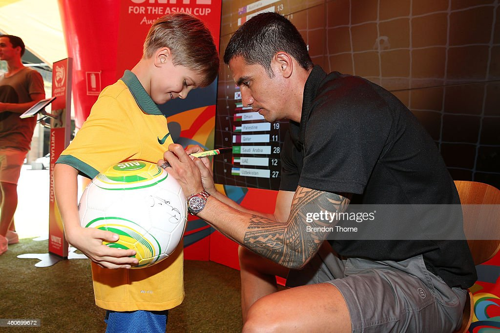 Australian Socceroos player Tim Cahill signs an autograph for a young fan during the launch of the Football Fan Park at Customs House on December 20, 2014 in Sydney, Australia.