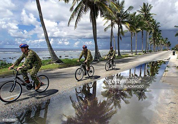 Australian soldiers use mountain bikes to get around the flooded streets of Nauru 14 September 2001 in order to conserve fossil fuel and maintain...