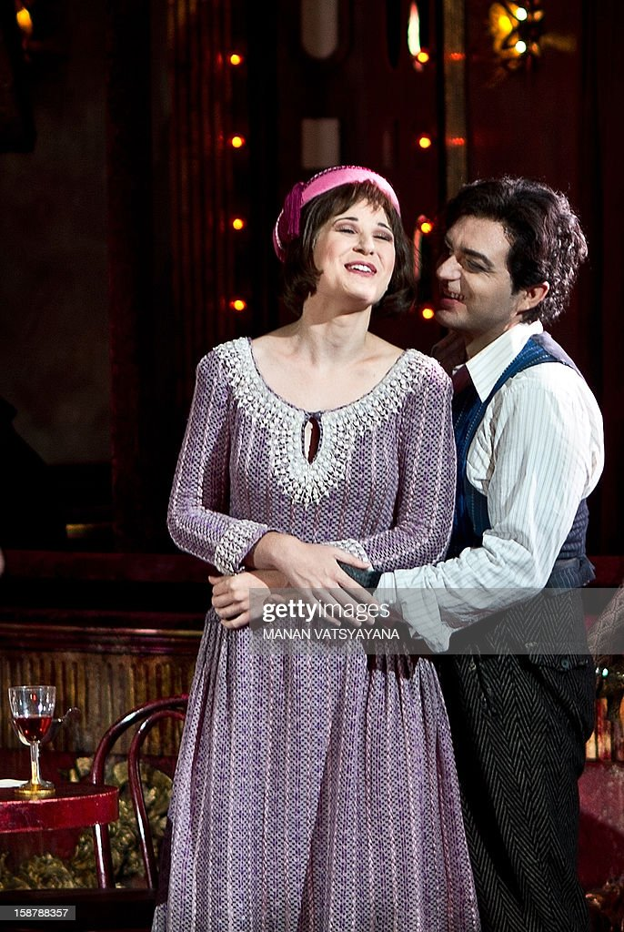 Australian soprano Nicole Car (L) and Italian tenor Gianluca Terranova (R) perform in the roles of Mimi and Rodolfo during a full dress rehearsal for Gale Edward's production 'La Boheme' at the Sydney Opera House on December 29, 2012. Australian Opera director Gale Edward's adaptation of Puccini's La Behome which opens in Sydney on New Years eve, centers on a group of bohemian friends - a poet, a philosopher, a musician and a painter. AFP PHOTO / MANAN VATSYAYANA