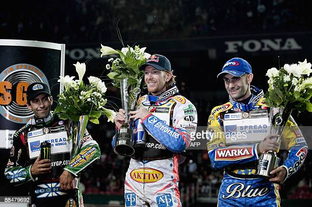 Australian speedway rider Jason Crump stands on the winners podium with runner up Greg Hancock of the US and Tomasz Gollob of Poland who placed third...