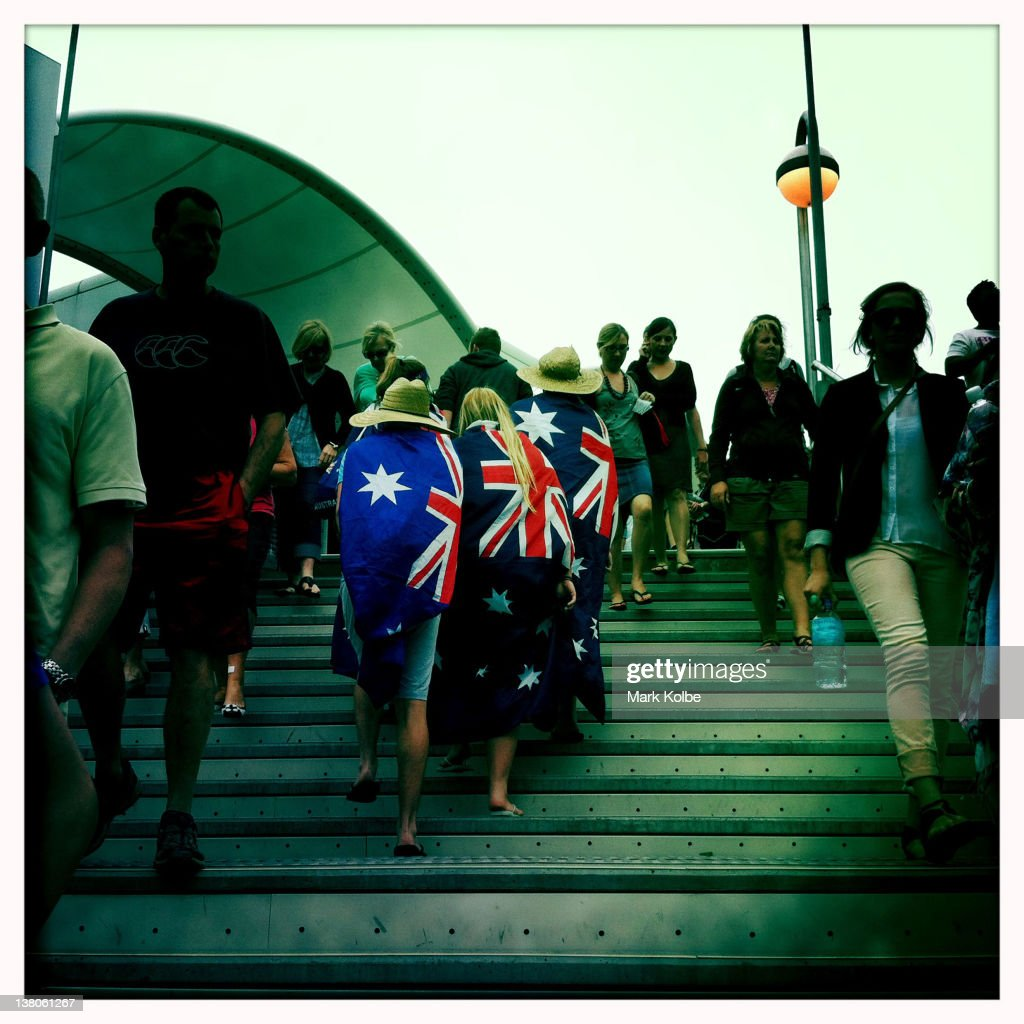 Australian supporters wearing Australian flags walk up the stairs toward Rod Laver Arena during day five of the 2012 Australian Open at Melbourne...