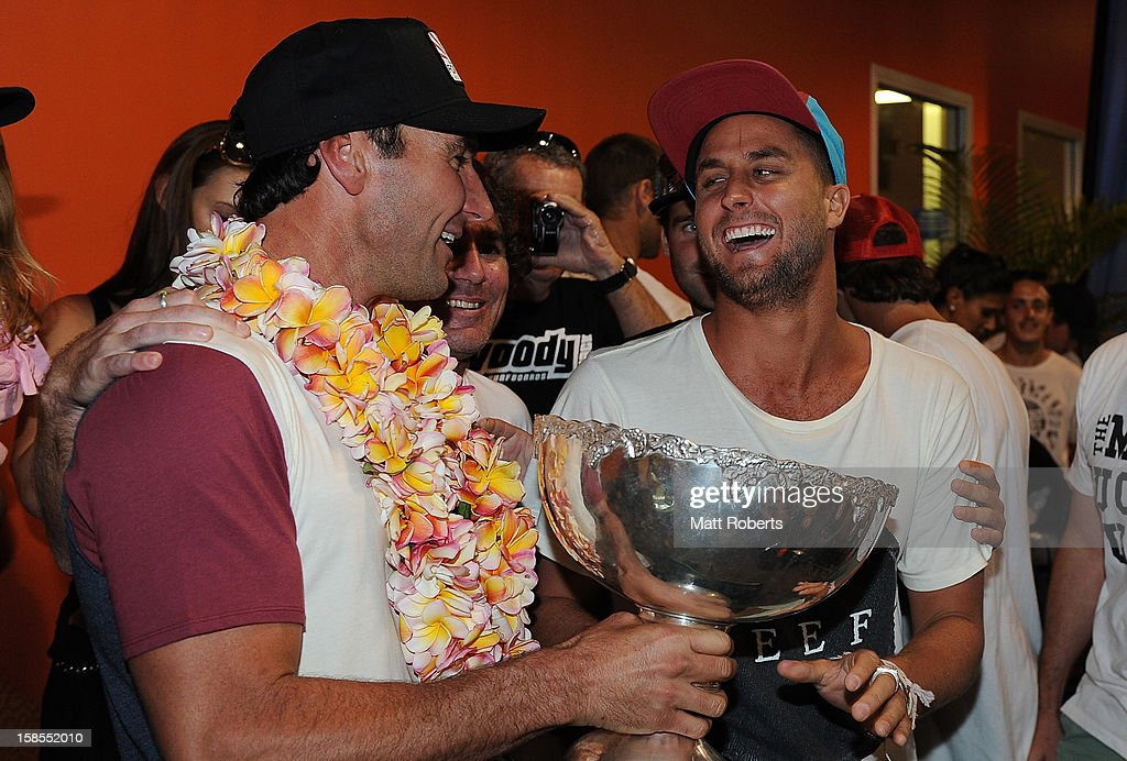 Australian surfer <a gi-track='captionPersonalityLinkClicked' href=/galleries/search?phrase=Joel+Parkinson&family=editorial&specificpeople=234875 ng-click='$event.stopPropagation()'>Joel Parkinson</a> is congratulated by Paul Fisher (R) as he arrives home at the Gold Coast airport on December 19, 2012 on the Gold Coast, Australia. Parkinson won the Pipeline Masters and his first ASP World Title on Monday.