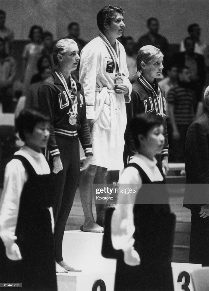 Australian swimmer Dawn Fraser with her gold medal on the rostrum after winning the 100 Metres Freestyle at the Yoyogi National Gymnasium, Tokyo, 15th October 1964. Americans Sharon Stouder (left) and Kathleen Ellis won silver and bronze medals respectively.
