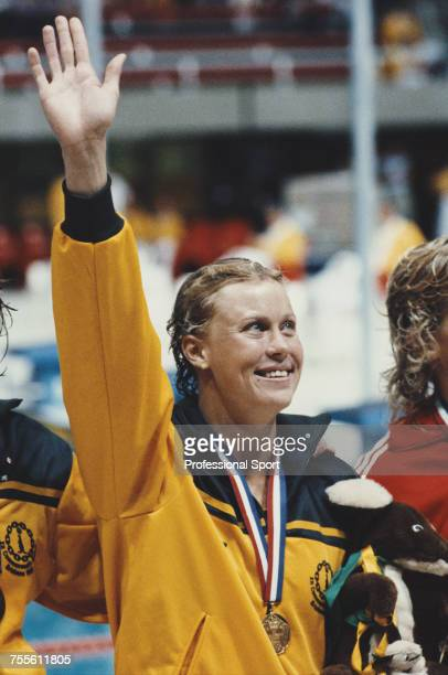Australian swimmer Lisa Curry raises one arm in the air on the medal podium at a medal ceremony in the Chandler Aquatic Centre during the 1982...