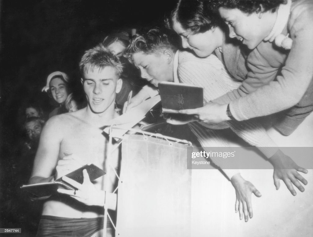 Australian swimmer Murray Rose, winner of the 400-metre crawl at the Melbourne Olympics, signs autographs for young fans, 4th December 1956. Rose won two other gold medals at Melbourne, for the 1,500 metres and the 4x200 metres freestyle relay.