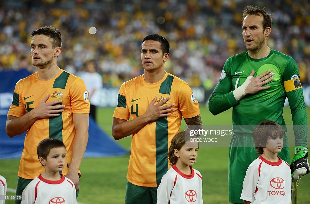 Australian team members James Holland (L), Tim Cahill (C) and captain Mark Schwarzer (R), stand for the national anthem prior to the start of their World Cup football qualifier against Oman in Sydney on March 26, 2013. Brett Holman helped Australia keep their World Cup qualifying hopes alive with a late long-range goal that ensured a 2-2 draw and denied a fighting Oman an upset victory. IMAGE STRICTLY RESTRICTED TO EDITORIAL USE - STRICTLY NO COMMERCIAL USE AFP PHOTO / Greg WOOD
