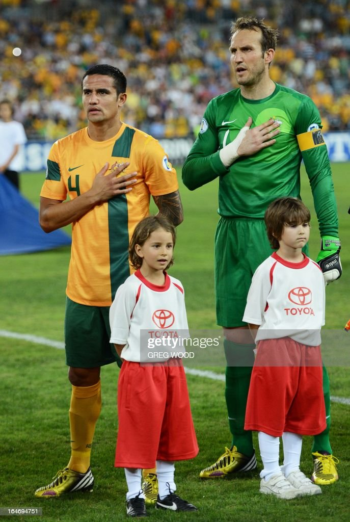 Australian team members Tim Cahill (L) and captain Mark Schwarzer (R) stand for the national anthem prior to the start of their World Cup football qualifier against Oman in Sydney on March 26, 2013. Brett Holman helped Australia keep their World Cup qualifying hopes alive with a late long-range goal that ensured a 2-2 draw and denied a fighting Oman an upset victory. IMAGE STRICTLY RESTRICTED TO EDITORIAL USE - STRICTLY NO COMMERCIAL USE AFP PHOTO / Greg WOOD
