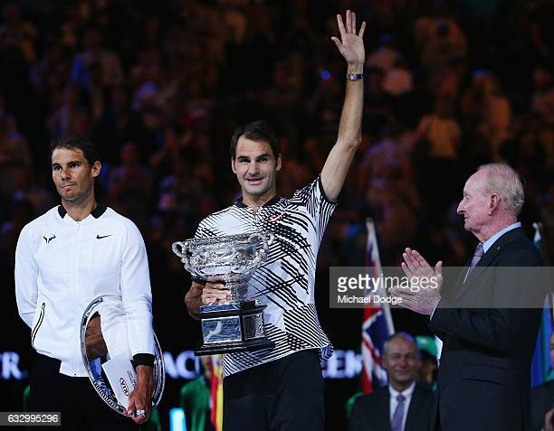 Australian tennis legend Rod Laver claps as a defeated Raphael Nadal of Spain reacts when Roger Federer of Switzerland celebrates with the Trophy...