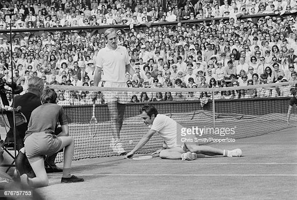 Australian tennis player John Newcombe pictured lying on the floor of centre court during play before winning the final of the Men's Singles...