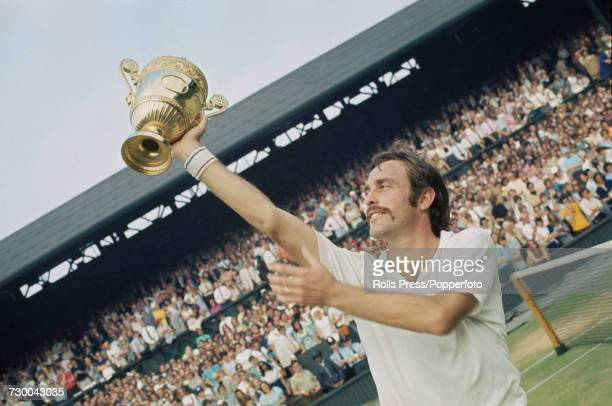 Australian tennis player John Newcombe pictured raising the Gentlemen's Singles Trophy in the air after defeating Stan Smith to win the final of the...