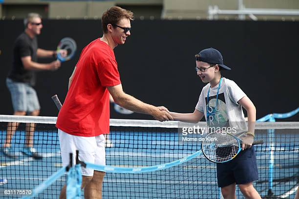 Australian tennis player John Peers shakes hands with a young player after playing tennis with them at Memorial Drive Tennis court during the 2017...