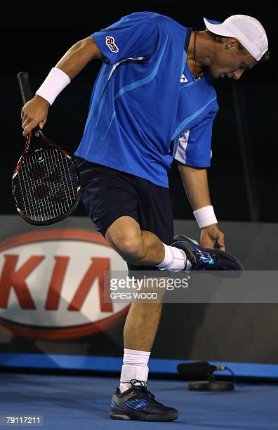 Australian tennis player Lleyton Hewitt checks the soles of his shoes during his mens singles match against Cypriot opponent Marcos Baghdatis at the...
