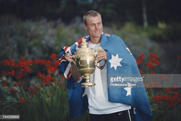 Australian tennis player Lleyton Hewitt wrapped in the national flag of Australia holds the Gentlemen's Singles Trophy after beating David Nalbandian...