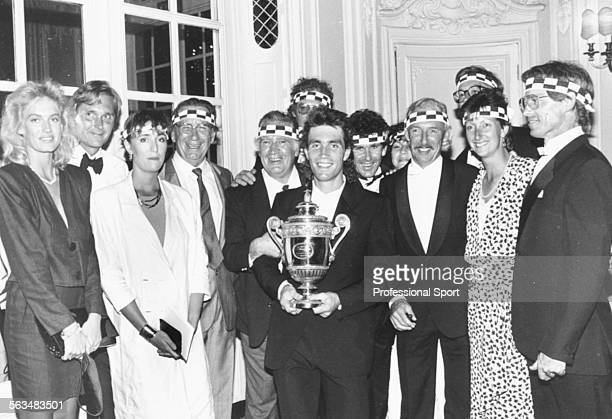 Australian tennis player Pat Cash holds his Wimbledon Tennis Championship trophy surrounded by family members wearing his distinctive chequered sweat...