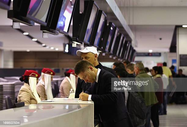 Australian Test captain Michael Clarke checks in before leaving for the ICC Champions League and the Ashes Tour at Sydney International Airport on...