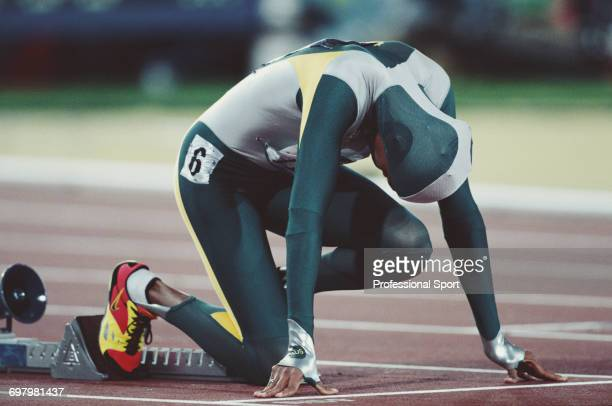Australian track athlete Cathy Freeman pictured wearing a one piece body suit in the starting blocks prior to finishing in first place to win the...