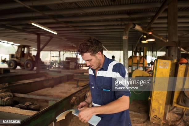 Australian tradesman working in sawmill writing invoice