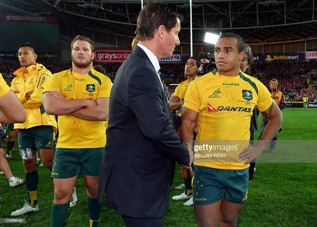 Australian Wallabies coach Robbie Deans (C) shakes hands with halfback Will Genia (R) after their loss to the British and Irish Lions in the third rugby Test match played in Sydney on July 6, 2013. AFP PHOTO/William WEST IMAGE