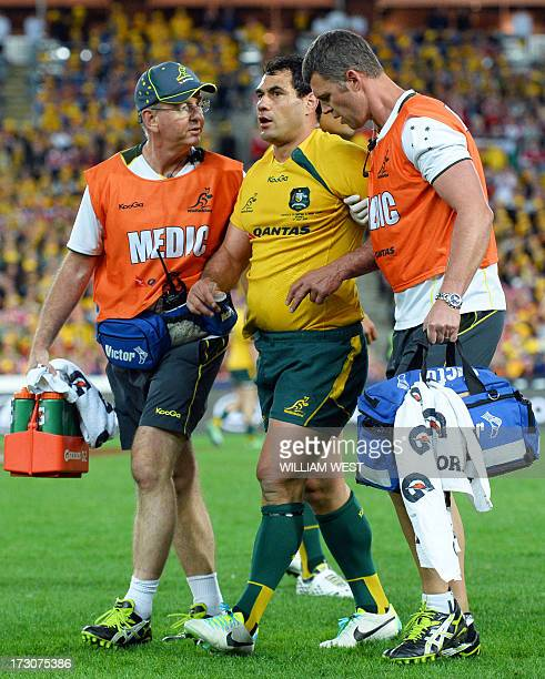 Australian Wallabies flanker George Smith is helped off the pitch after a head clash during the third rugby Test match against the British and Irish...