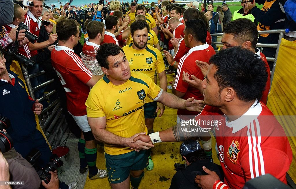 Australian Wallabies flanker George Smith (C) shakes hands with British and Irish Lions centre Manu Tuilagi (R) after the Lions defeat the Australian Wallabies in the third rugby Test match played in Sydney on July 6, 2013. AFP PHOTO/William WEST IMAGE