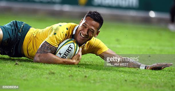 Australian Wallabies player Israel Folau dives over to score a try against England in their international rugby union match played in Brisbane on...