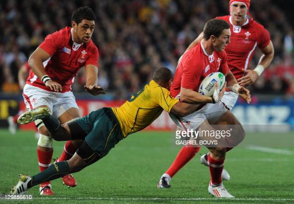 Australian Wallabies scrumhalf Will Genia tackles Wales' wing George North as Wales' flanker Toby Faletau looks on during the 2011 Rugby World Cup...