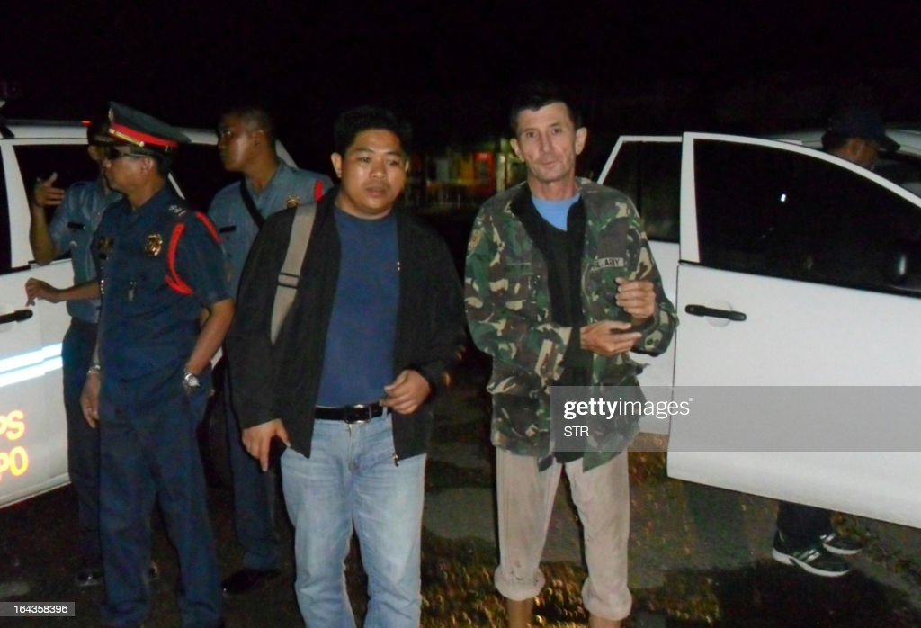 Australian Warren Rodwell (front R) is escorted by Philippine police officers as he arrives at a police station in Pagadian City, on the southern island of Mindanao early March 23, 2013, shortly after he was released by his Islamic militant kidnappers. Rodwell walked free on March 23 after being held for 15 months by Islamic militants in the lawless southern Philippines, deeply emaciated and frail but able to smile.
