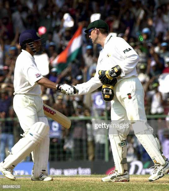 Australian wicketkeeper Adam Gillchirst congratulates Indian batsman Sachin Tendulkar after he completed a century during the third day of their...
