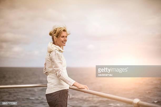 Australian woman contemplating sunrise next to the sea