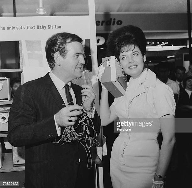 Australianborn British disc jockey Alan 'Fluff' Freeman presents Miss World winner Rosemarie Frankland with a baby alarm radio at the Radio Show at...