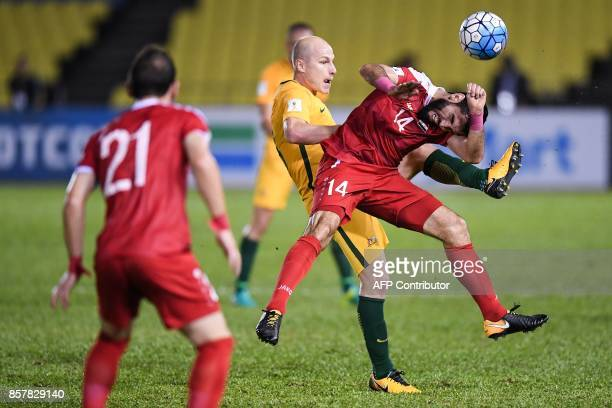 Australia's Aaron Mooy and Syria's Yousef Kalfa compete for the ball during the 2018 World Cup qualifying football match between Syria and Australia...