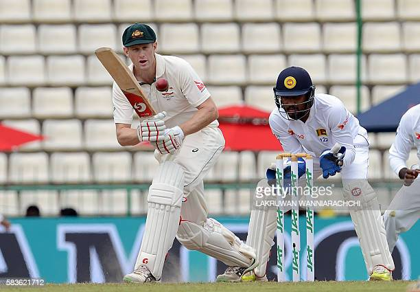 Australia's Adam Voges plays a shot as Sri Lanka's wicketkeeper Dinesh Chandimal looks on during the second day of their opening Test match between...