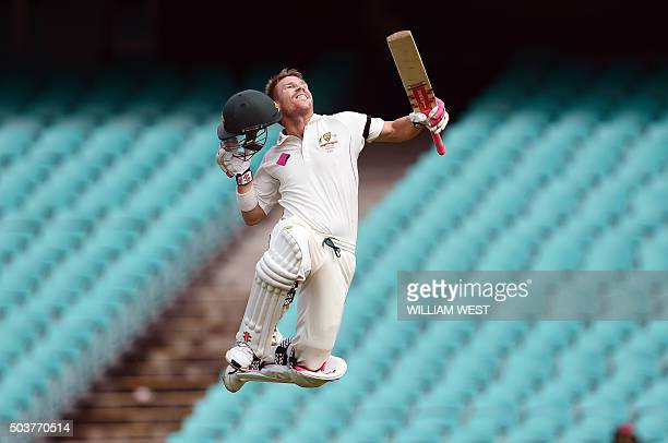 TOPSHOT Australia's batsman David Warner leaps in the air after scoring his century against the West Indies on the final day of the third cricket...