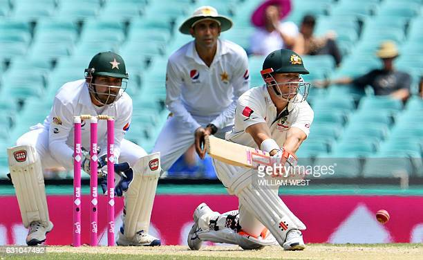 Australia's batsman David Warner plays a reverse sweep as Pakistan wicketkeeper Sarfraz Ahmed and Younis Khan look on on the fourth day of the third...