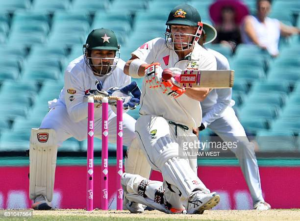 Australia's batsman David Warner sweeps from the Australian bowling as Pakistan wicketkeeper Sarfraz Ahmed looks on on the fourth day of the third...