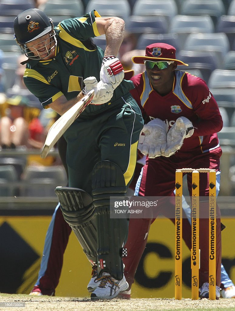 Australia's batsman George Bailey (L) drives as West Indies wicketkeeper Johnson Charles (R) watches during the one-day international cricket match between Australia and the West Indies at the WACA ground in Perth on February 3, 2013. AFP PHOTO/Tony ASHBY IMAGE