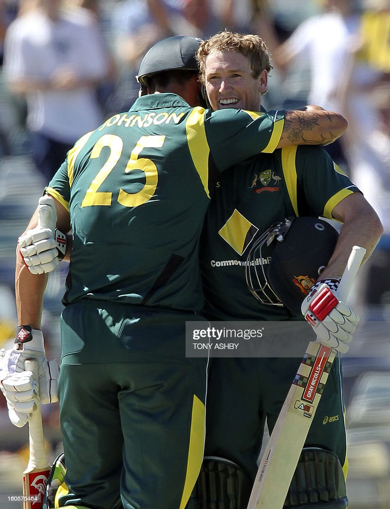 Australia's batsman George Bailey (R) is congratulated by teammate Mitchell Johnson (L) after scoring a century during the one-day international cricket match between Australia and the West Indies at the WACA ground in Perth on February 3, 2013. AFP PHOTO/Tony ASHBY USE