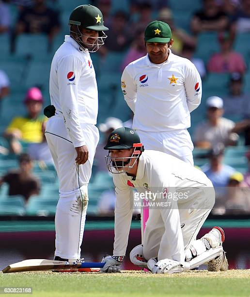 Australia's batsman Matt Renshaw regains his feet after being hit on the helmet by a bouncer as Sharjeel Khan and Sarfraz Ahmed of Pakistan look on...
