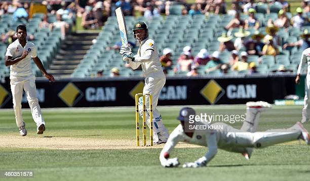Australia's batsman Michael Clarke looks back as India's wicketkeeper Wriddhiman Saha dives to stop the ball on the fourth day of the first Test...