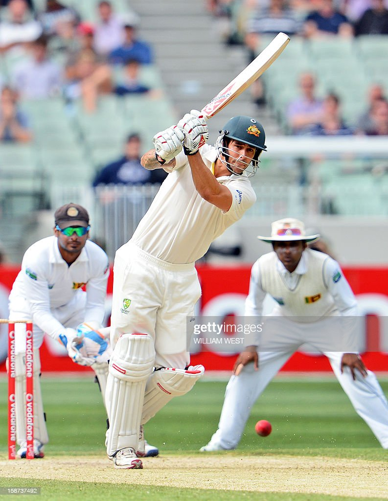 Australia's batsman Mitchell Johnson (C) pulls a delivery from the Sri Lankan bowling as wicketkeeper Kumar Sangakkara (L) and Mahela Jayawardene (R) look on on the second day of the second cricket Test match at the Melbourne Cricket Ground (MCG) on December 27, 2012. AFP PHOTO/William WEST USE