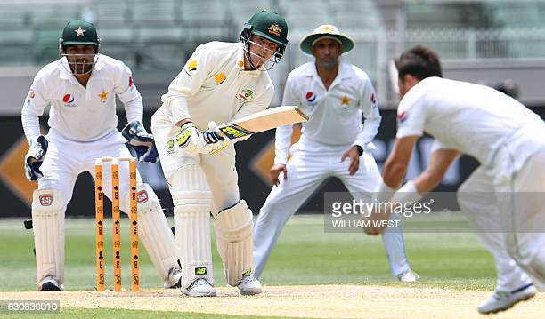 Australia's batsman Nic Maddinson hits the ball back to Pakistan spinner Yasir Shah as wicketkeeper Sarfraz Ahmed and fieldsman Younis Khan look on...