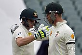 Australia's batsman Steve Smith hugs team captain Michael Clarke as he reaches his century during the second day of the first Test cricket match...