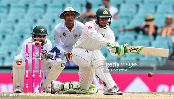 Australia's batsman Usman Khawaja sweeps a delivery as Pakistan wicketkeeper Sarfraz Ahmed and Younis Khan look on on the fourth day of the third...
