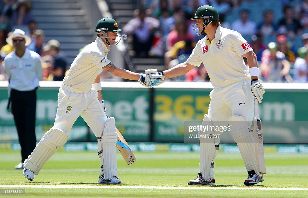 Australia's batsmen Michael Clarke (L) and Shane Watson (R) shake hands after their 100 run partnership against Sri Lanka on the second day of the second cricket Test match at the Melbourne Cricket Ground (MCG) on December 27, 2012. AFP PHOTO/William WEST USE