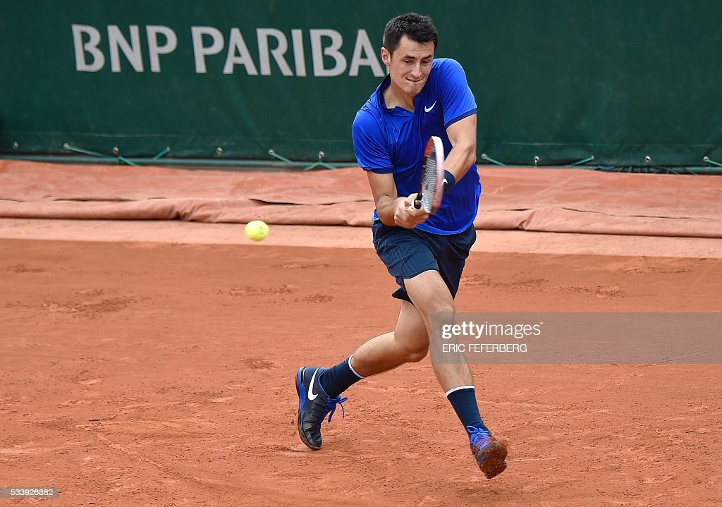 Australia's Bernard Tomic hits a return to US Brian Baker during their men's first round match at the Roland Garros 2016 French Tennis Open in Paris on May 24, 2016. / AFP / Eric FEFERBERG