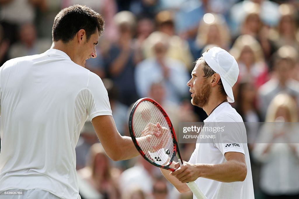 Australia's Bernard Tomic (L) shakes hands with Moldova's Radu Albot (R) after Tomic won their men's singles second round match on the fourth day of the 2016 Wimbledon Championships at The All England Lawn Tennis Club in Wimbledon, southwest London, on June 30, 2016. / AFP / ADRIAN