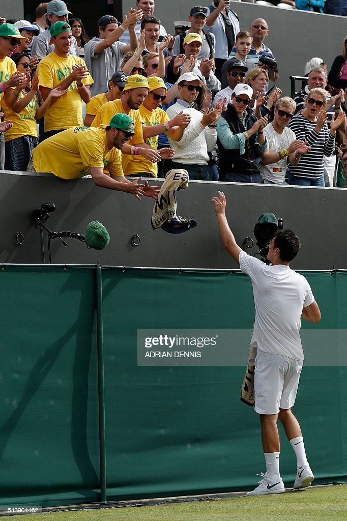 Australia's Bernard Tomic throws his towel to the Australian fans in the crowd after he beat Moldova's Radu Albot during their men's singles second round match on the fourth day of the 2016 Wimbledon Championships at The All England Lawn Tennis Club in Wimbledon, southwest London, on June 30, 2016. / AFP / ADRIAN
